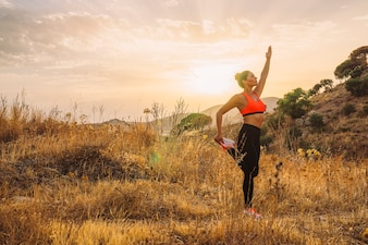 Une femme équilibrée s'étendant dans la nature