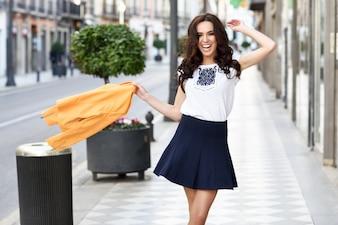 Une jeune femme brune souriante en milieu urbain.