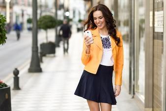 Une jeune femme brune souriante et regarde son téléphone intelligent