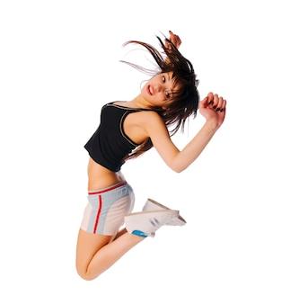 Une jeune fille excitée qui saute sur le blanc