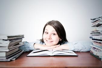 Une jeune fille mignonne intelligente qui étudie.