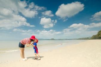 Une mère et un fils sur la plage à l'extérieur Mer et ciel bleu