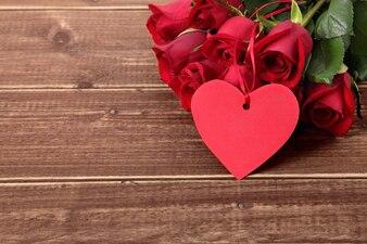 Valentine étiquette de cadeau et des roses sur planche de bois