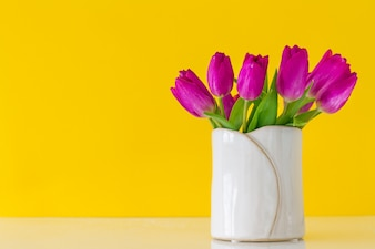 Vase blanc avec des tulipes pourpres sur un fond jaune