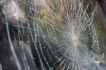 Verre cassé fissures éclats devant voiture. (Image filtrée
