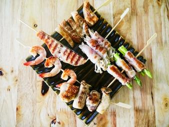 Viande de poulet frit et barbecue aux fruits de mer avec des légumes sur des brochettes de bois sur une sauce à la planche. Vue de dessus