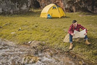Voyageur avec une carte assise sur la pelouse