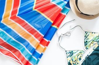 Vue aérienne des articles d'été avec un parapluie coloré, des maillots de bain et un chapeau sur fond blanc