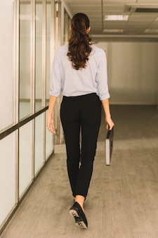Vue arrière de la femme d'affaires marchant