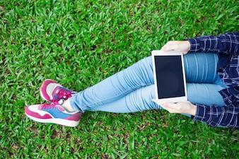Vue croisée de la fille utilisant la tablette sur l'herbe