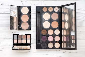Vue de dessus de la palette de maquillage rose et marron sur fond blanc en bois