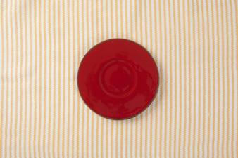 Vue de dessus de la plaque rouge vide, placez la table en tissu avec un espace pour la copie.