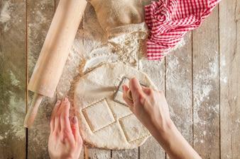 Vue de dessus des mains coupant la pâte