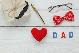"""Vue de dessus Happy Father day .Red heart and word """"DAD"""" sur fond de bois rustique. Accessoires avec moustache, cravate vintage, stylo, cadeau et lunettes."""