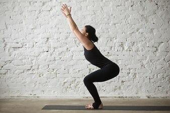 Young yogi attractive woman in Utkatasana pose, loft blanc arrière