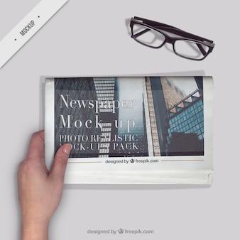 A pessoa que lê um jornal com um óculos na área de trabalho