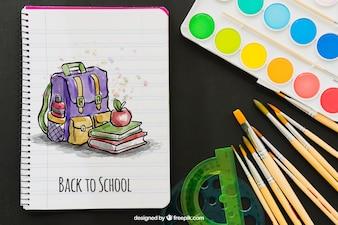 Aguarelas, pincéis e caderno com desenho colorido