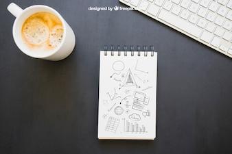 Caderno com desenhos, caneca de café e teclado