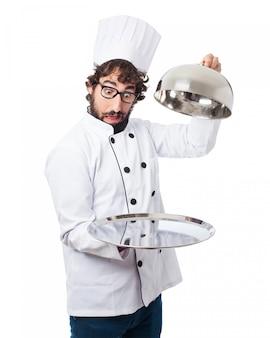 Cocinero con una bandeja vacia