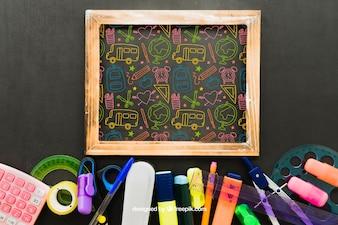 Desenho colorido no quadro-negro e material escolar
