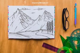 Desenho de lápis de montanhas com óculos, canetas e ramos