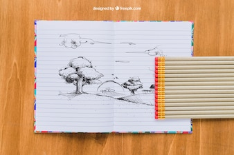 Desenho de lápis em caderno, lápis e fundo de madeira
