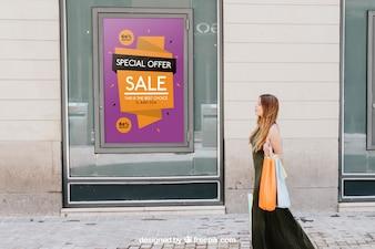 Design de maquete com cartaz de vendas e mulher na rua