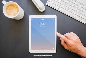 Escritorio de oficina y dedo tocando la tablet en vertical