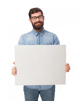 Hombre con camisa vaquera sujetando un cartel en blanco