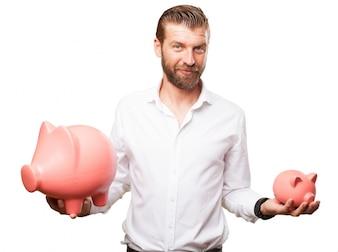 Hombre de negocios sujetando dos huchas de diferentes tamaños