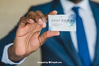 Homem de negócios que mostra o cartão de visita perto