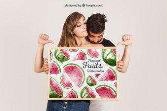 Jovem casal apresentando quadro branco