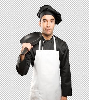 Jovem cozinheiro chefe usando um utensílio de cozinha com um gesto de dúvida