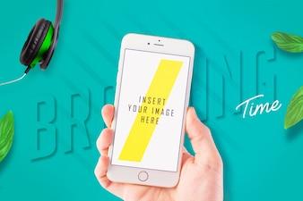 Mão segurando um smartphone com maquete