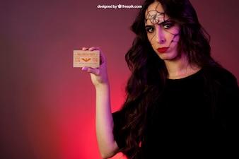 Maquete de Halloween com menina mostrando cartão