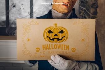 Mockup de halloween con hombre sujetando cartón
