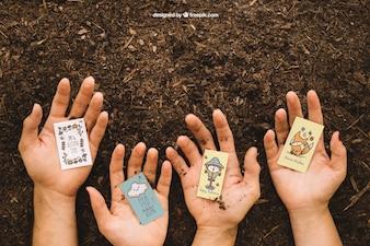 Mockup de jardinería con manos sujetando cartas