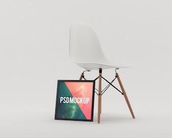 Moldura ao lado de uma cadeira branca mock up
