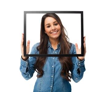 Mujer joven alegre posando con un marco