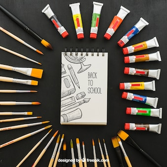 Pinturas y pinceles alrededor de la libreta