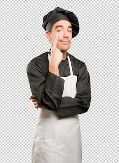 Preocupado jovem cozinheiro observando