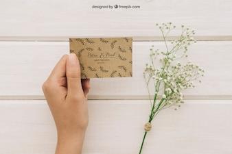 Ramo de flores y mano sujetando una tarjeta de boda