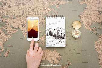 Smartphone, bloco de notas e bússola no mapa do mundo