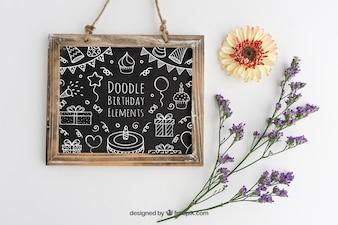 Conception Mockup avec de l'ardoise d'anniversaire et décoration florale