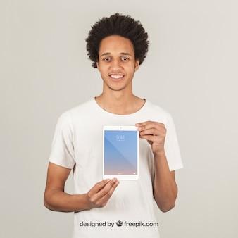 Jeune homme présentant une tablette