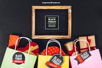 Maquette de vendredi noir avec ardoise et sacs pleins de cadeaux