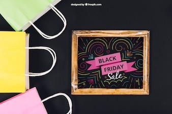 Maquette de vendredi noir avec ardoise et sacs