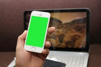 Smartphone avec écran vert dans la main avec un ordinateur portable de fond