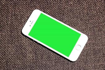 Mobile dello schermo verde con sfondo marrone