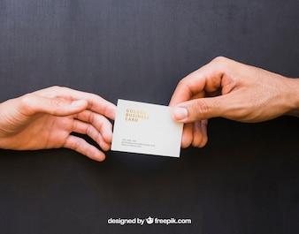 Mock up di mani che scambiano biglietto da visita d'oro